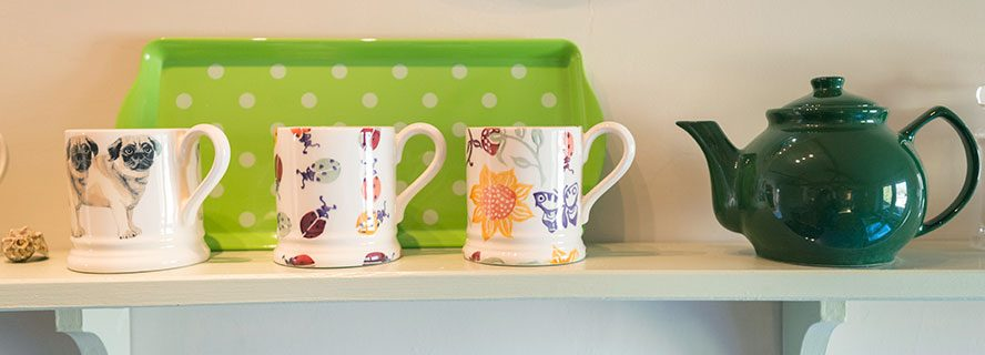 Mugs and teapot on shelf at holiday cottage